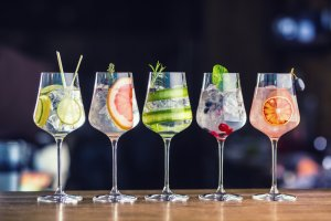 Five colorful gin tonic cocktails in wine glasses on bar counter in pup or restaurant.